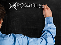 The word impossible written on a chalkboard with the first two letters crossed out